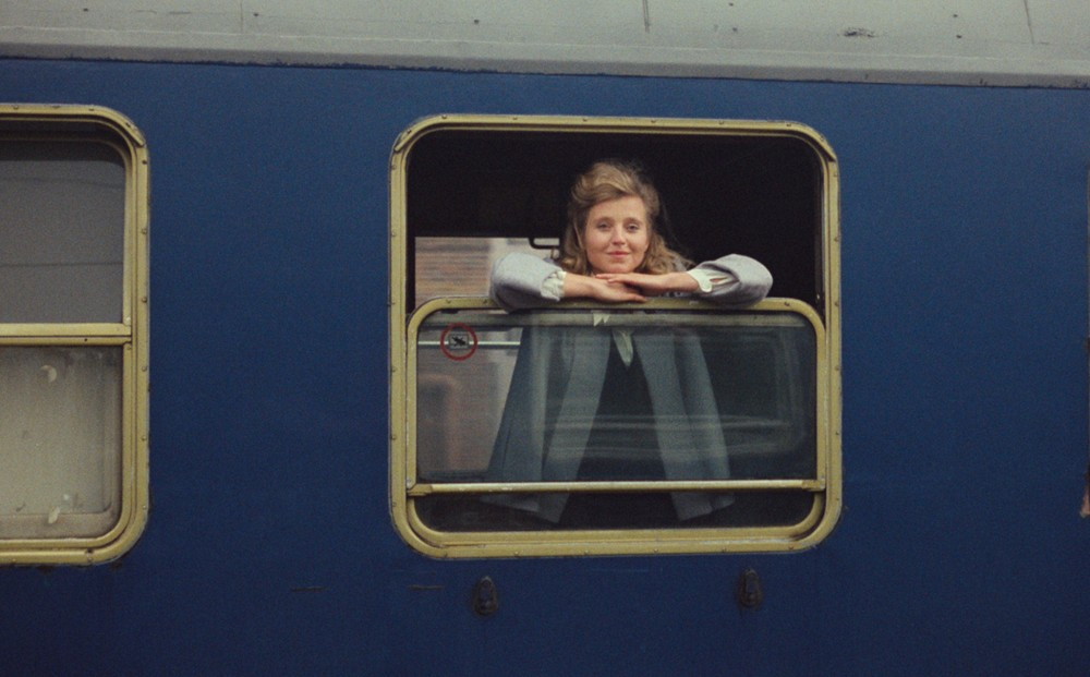 A woman looks out the window of a train car.