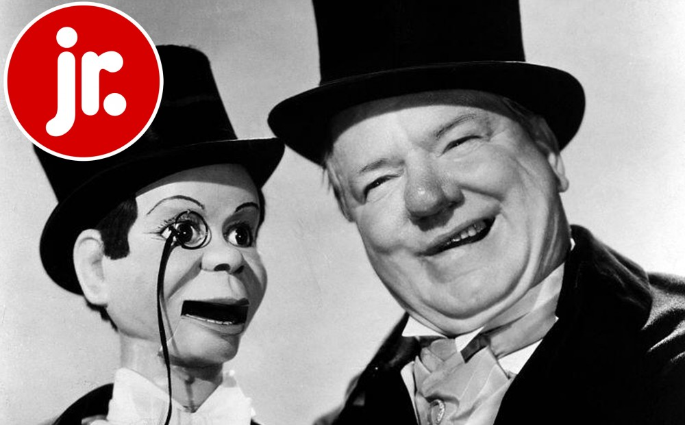 A man in a top hat smiles, next to a marionette in a top hat who wears a monocle.